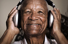 An older man smiling wearing headphones